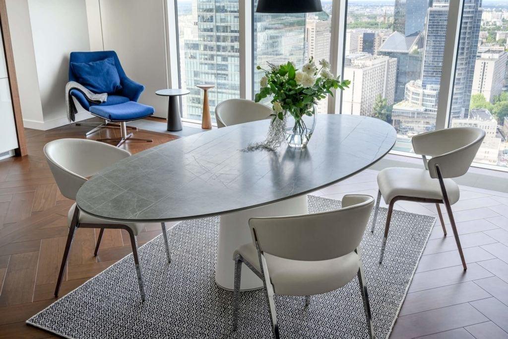 Duży stół w jadalni w apartamencie GLACE projektu pracowni AKSONOMETRIA