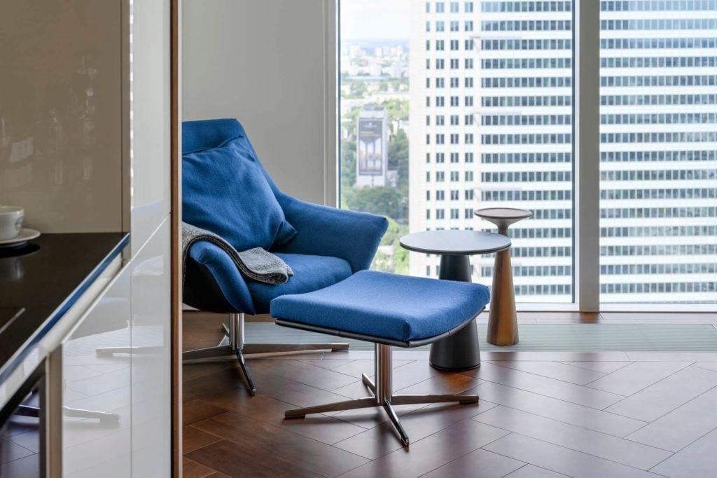 Niebieski fotel w apartamencie GLACE projektu pracowni AKSONOMETRIA