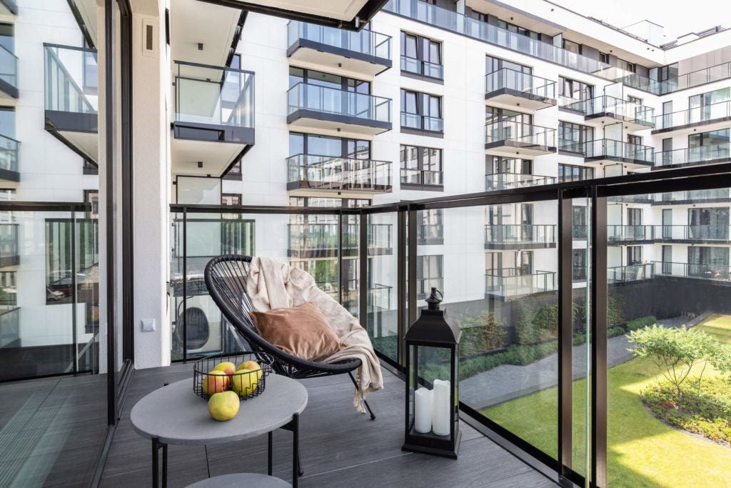 Duży balkon z fotelem i stolikiem