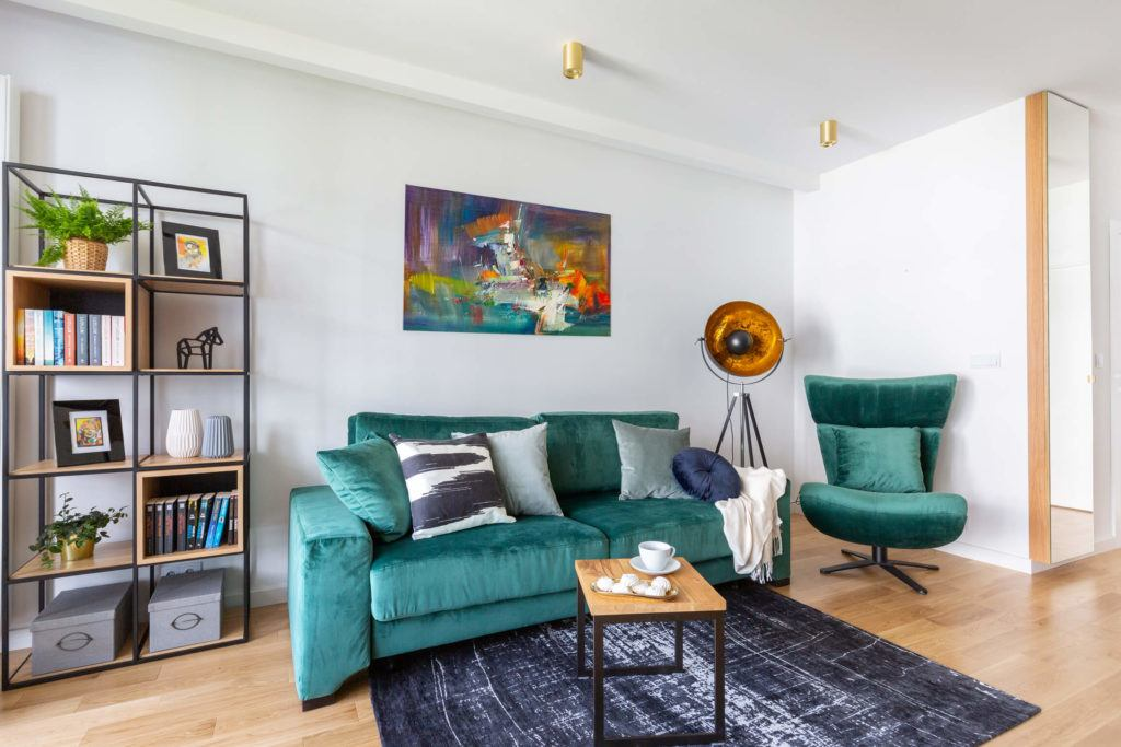Seledynowa sofa w salonie w mieszkaniu projektu pracowni Decoroom