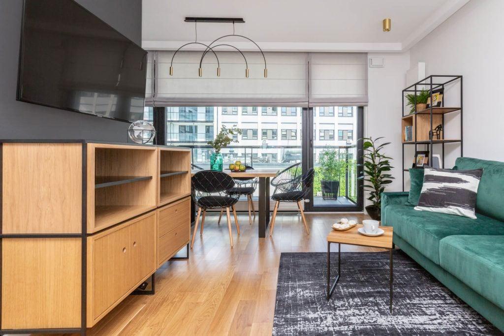 Salon z drewnianą podłogą w mieszkaniu projektu pracowni Decoroom