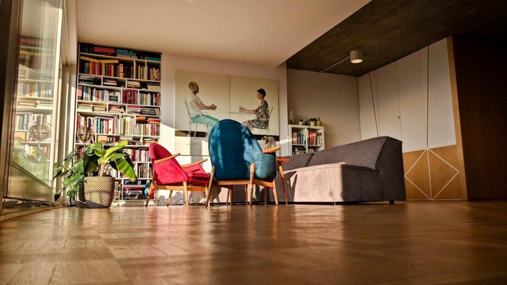 Drewniana podłoga, czerwony i niebieski fotel i duża sofa w kubistycznym apartamencie projektu Agnieszki Gansiniec z pracowni D44 architecture