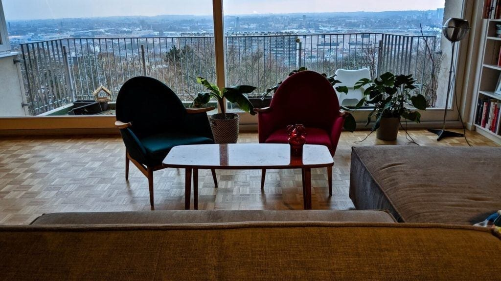 Dwa fotele stojące pod oknem w kubistycznym apartamencie projektu Agnieszki Gansiniec z pracowni D44 architecture