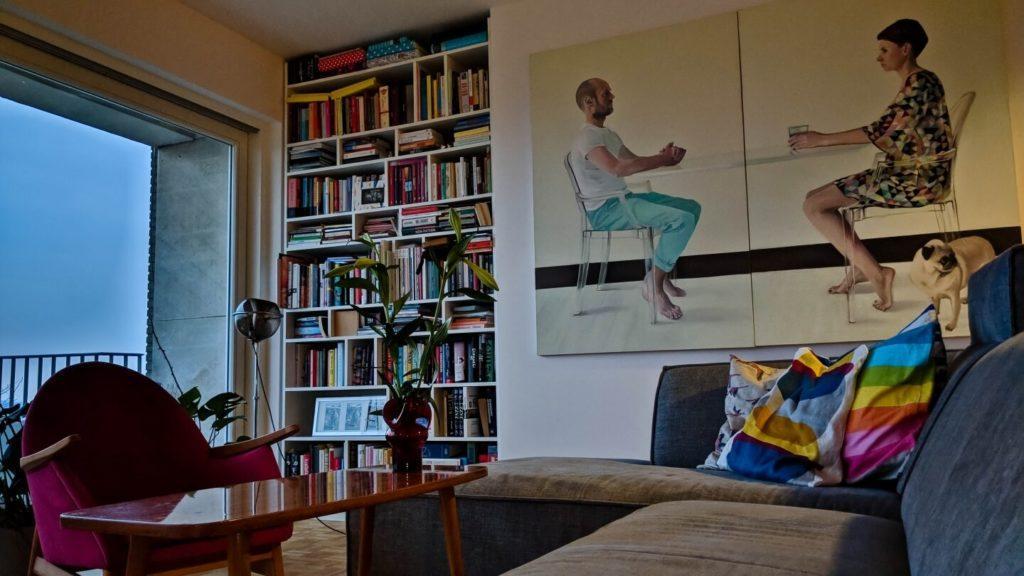 Regał z książkami i obraz na ścianie w kubistycznym apartamencie projektu Agnieszki Gansiniec z pracowni D44 architecture