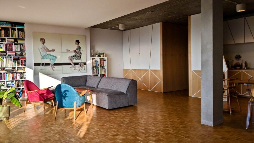Salon z drewnianą podłogą w kubistycznym apartamencie projektu Agnieszki Gansiniec z pracowni D44 architecture