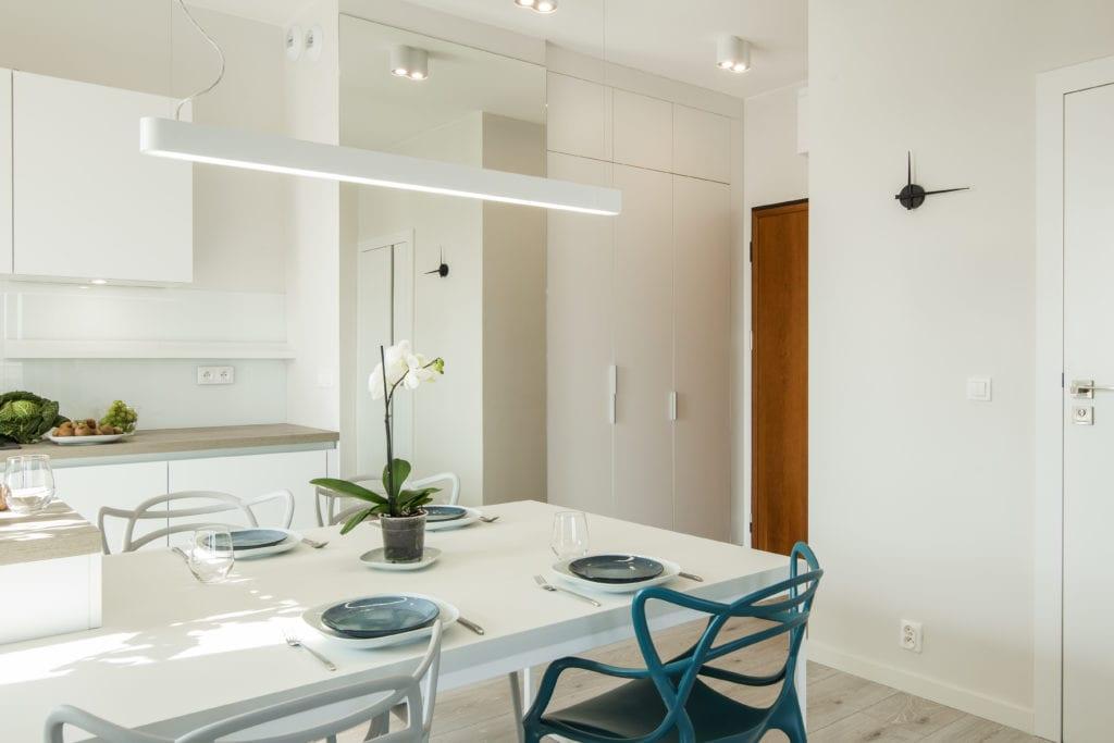 Białe wnętrze kuchni i jasny stół z rozstawioną zastawą