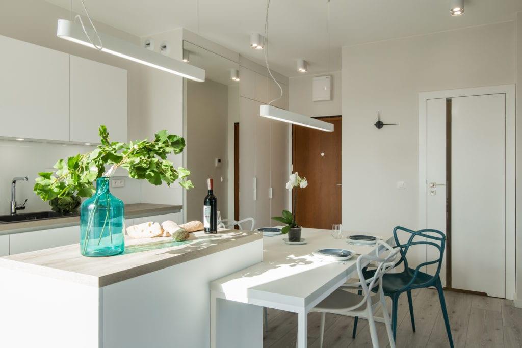 Biel we wnętrzach kuchni, dwa krzesła, stół i wiszące lampy