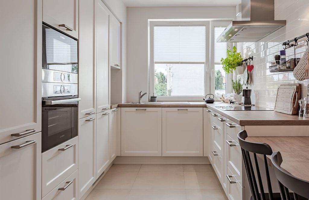 Biel we wnętrzu jasnej, dużej kuchni z zabudową kuchenną