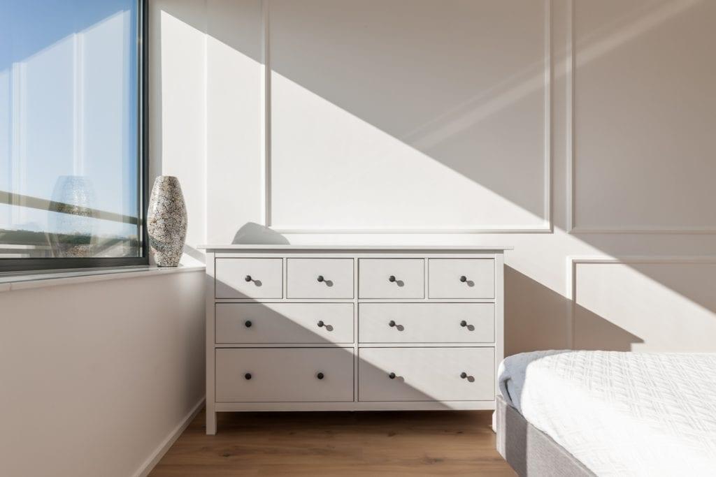 Biała komoda stojąca w pokoju z białą ścianą