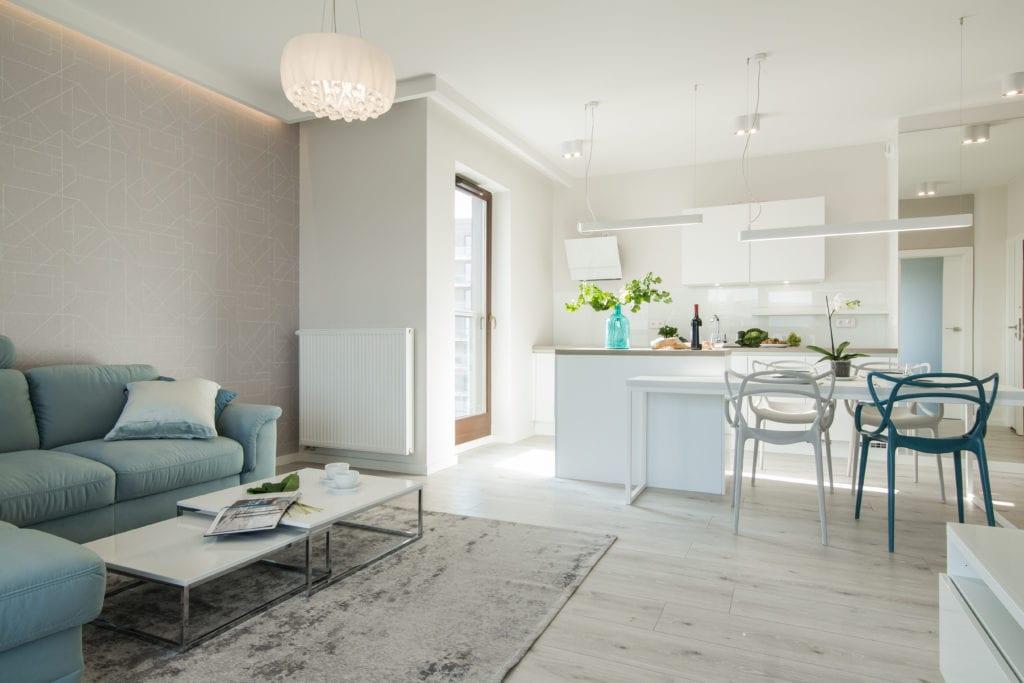 Biel we wnętrzach kuchni połączonej z salonem