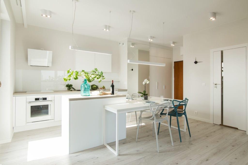Dwa krzesła stojące w jasnej kuchni projektu pracowni KODO