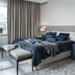 Łóżko w sypialni z niebieską pościeląw modernistycznej willi na Saskiej Kępie