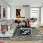 Salon z dużym, jasnym narożnikiemw modernistycznej willi na Saskiej Kępie