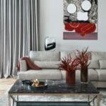 Salon z jasnym narożnikiem, stołem z czarnym blatem i obrazem na ścianie
