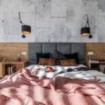 Aranżacja sypialni z dużym łóżkiem z szarym zagłówkiem