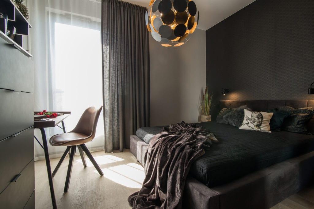 Sypialnia z dużym łóżkiem i wielką lampą wiszącą nad łóżkiem