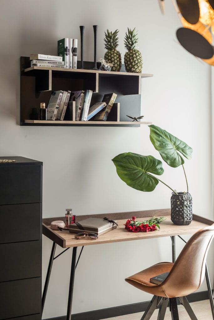Pokój z drewnianym biurkiem i zieloną rośliną