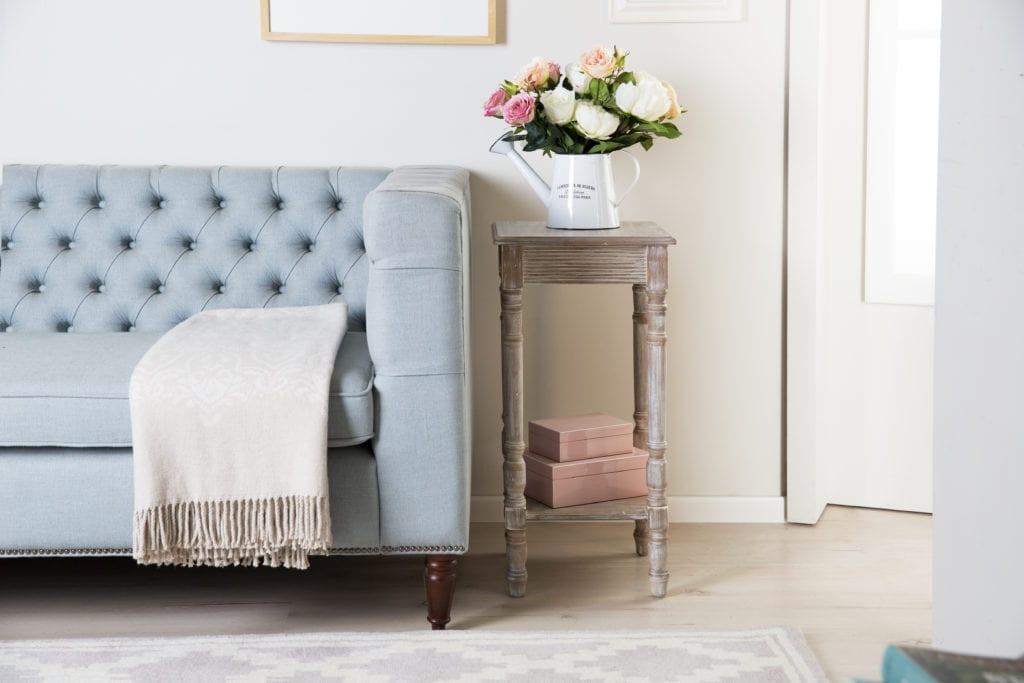 Pokój z pikowaną sofą w błękitnym kolorze