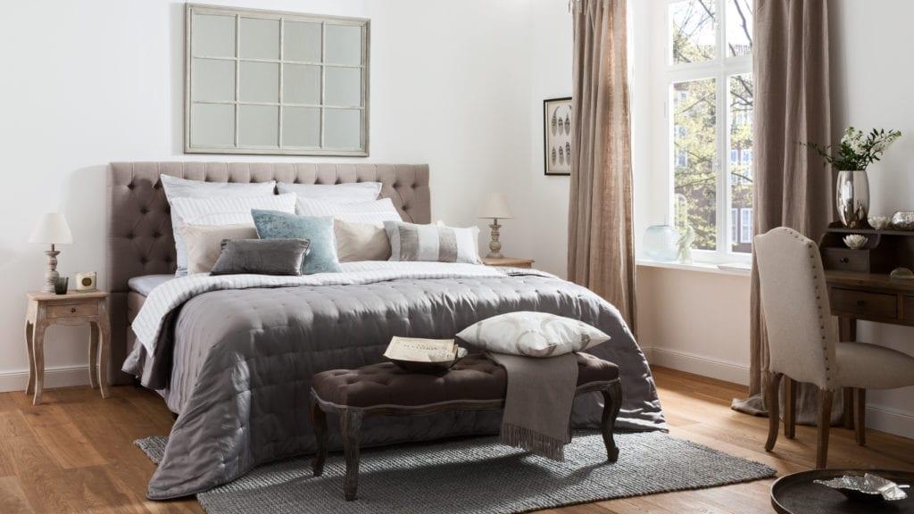 Sypialnia z dużym łóżkiem i szarą narzutą