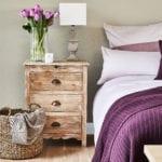 Sypialnia z dużym łózkiem, fioletową pościelą i drewnianą szafką
