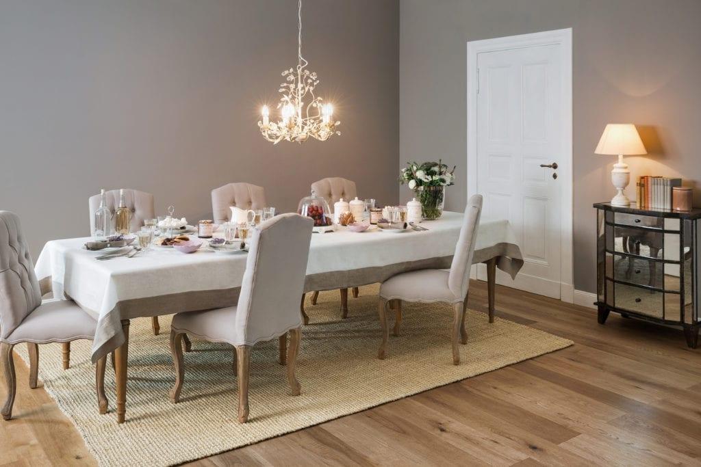 Salon z dużym stołem i szarą ścianą