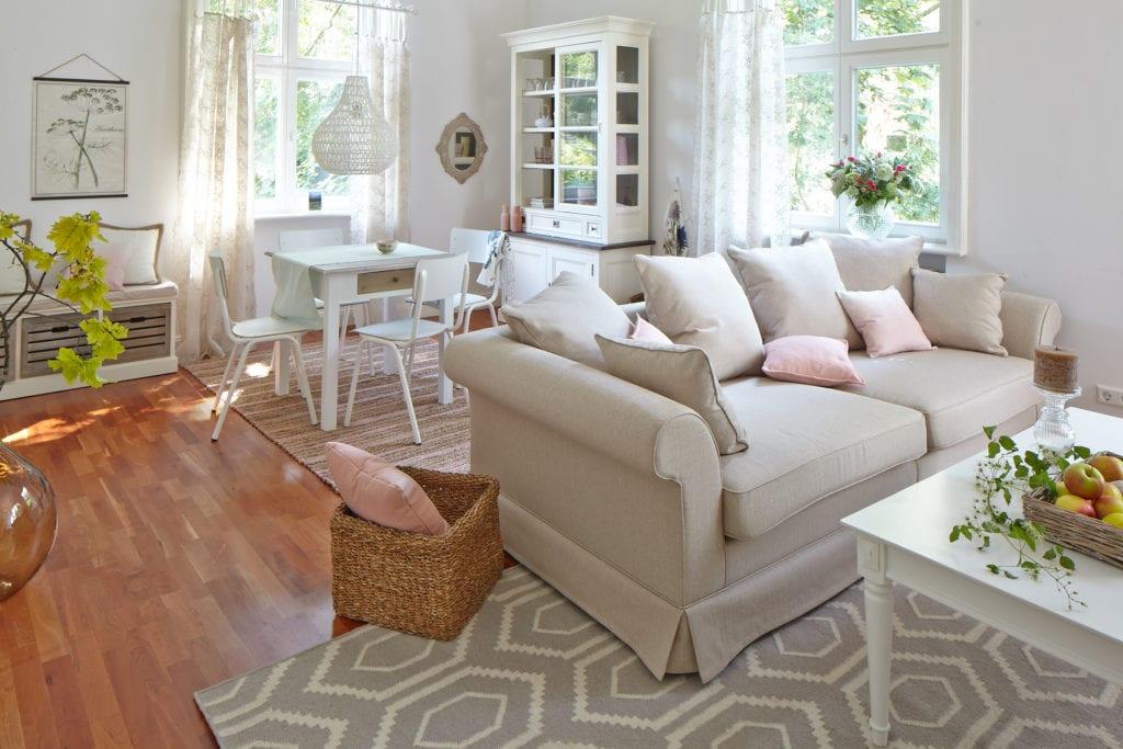 Salon z jasną, beżową sofą i drewnianą podłogą