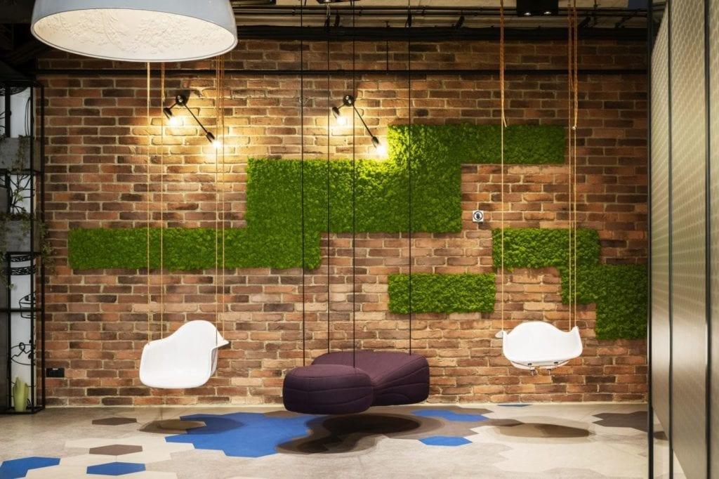 Ściana z cegły, zielony mech i huśtawka w biurze firmy Stalgast projektu MADAMA