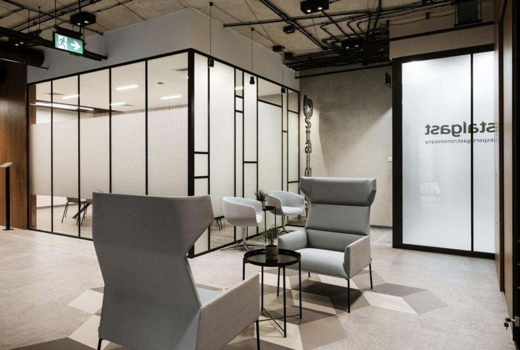 Szklany, przeszklony box i jasnoszare meble w biurze firmy Stalgast projektu MADAMA