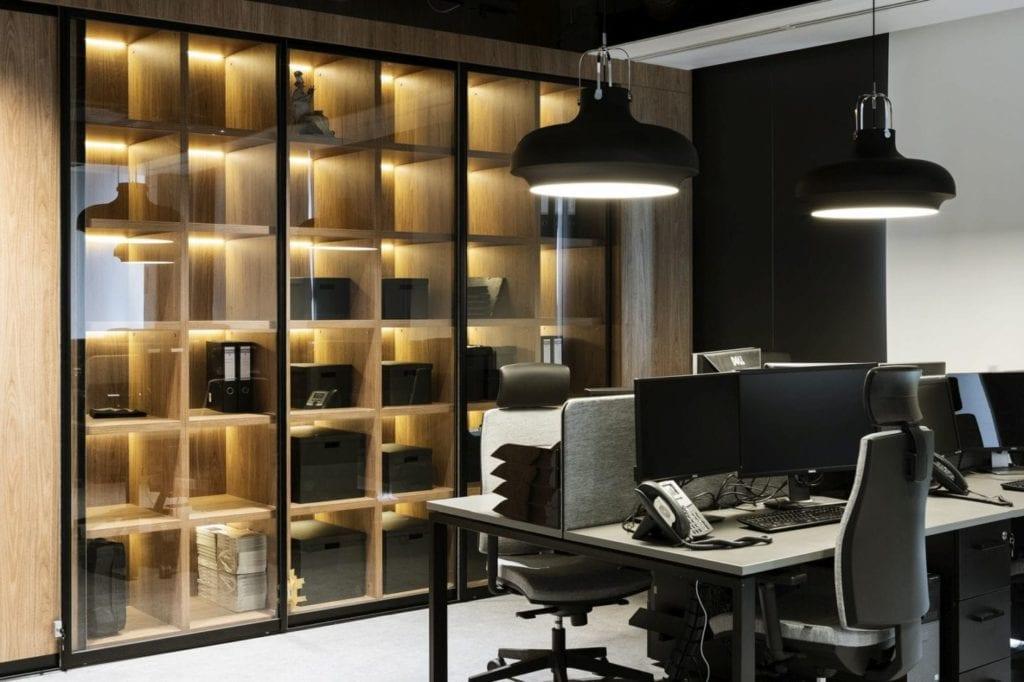 Czarna ściana i duży drewniany regał w biurze firmy Stalgast projektu MADAMA