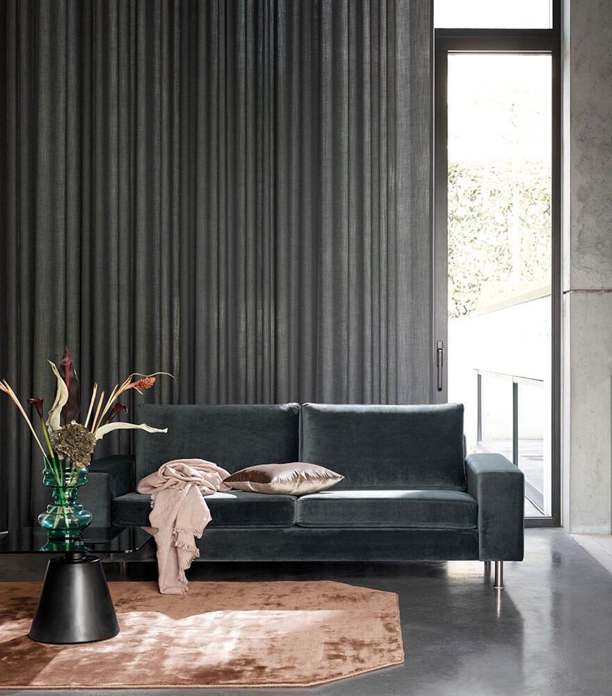 Czarna sofa Indivi stojąca w salonie z czarnymi zasłonami