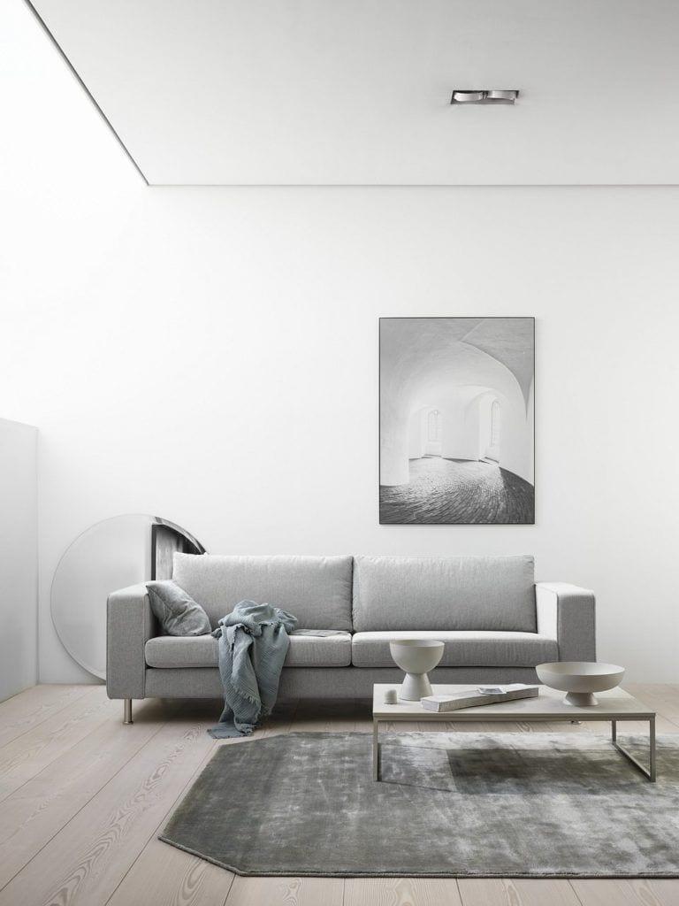 Szara sofa Indivi projektu Andersa Nørgaarda stojąca w jasnym pokoju z dużym obrazem