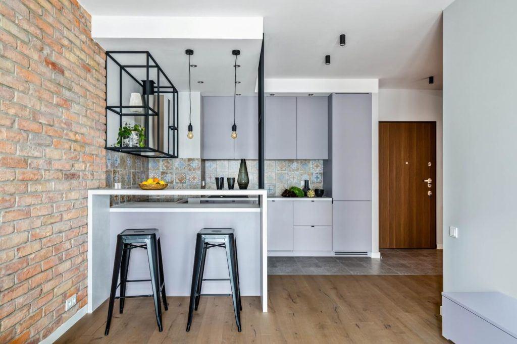 Kuchnia z białymi meblami i orientalnymi płytkami połączona z salonem z drewnianą podłogą i ścianą z cegły