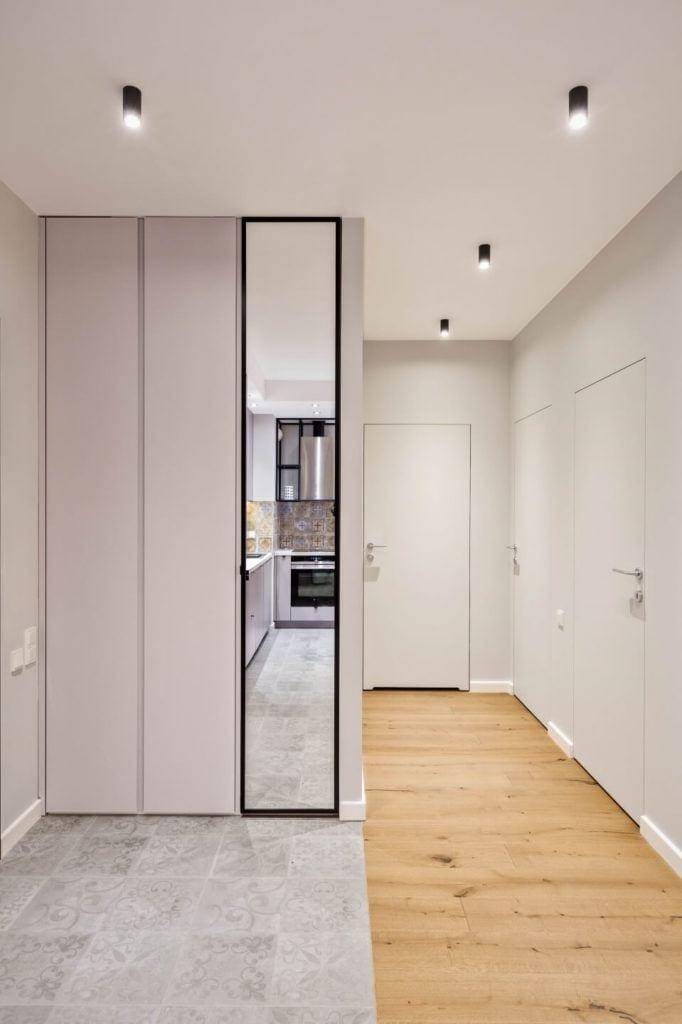 Przedpokój w apartamencie w stylu soft industrialnym z białą szafą z lustrem