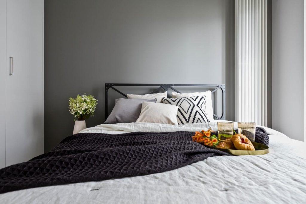 Duże łóżko w sypialni ze ścianą w szarym kolorze