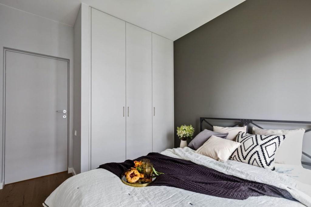 Szara sypialnia z białą szafą
