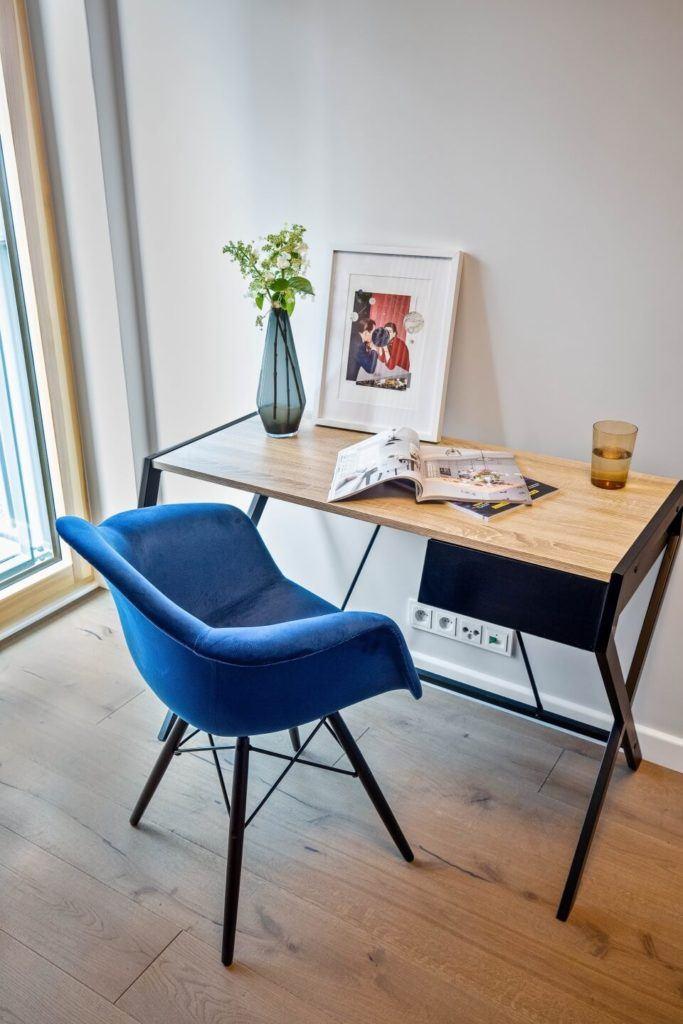 Drewniane biurko stojące pod ścianą i niebieski fotel