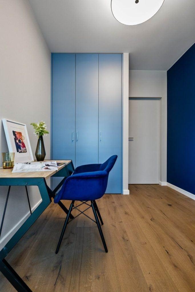 Pokój w apartamencie w stylu soft industrialnym z niebieską ścianą