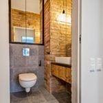 Toaleta w stylu soft industrialnym ze ścianą z cegły