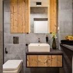 Łazienka z szarymi płytkami i drewnianymi detalami