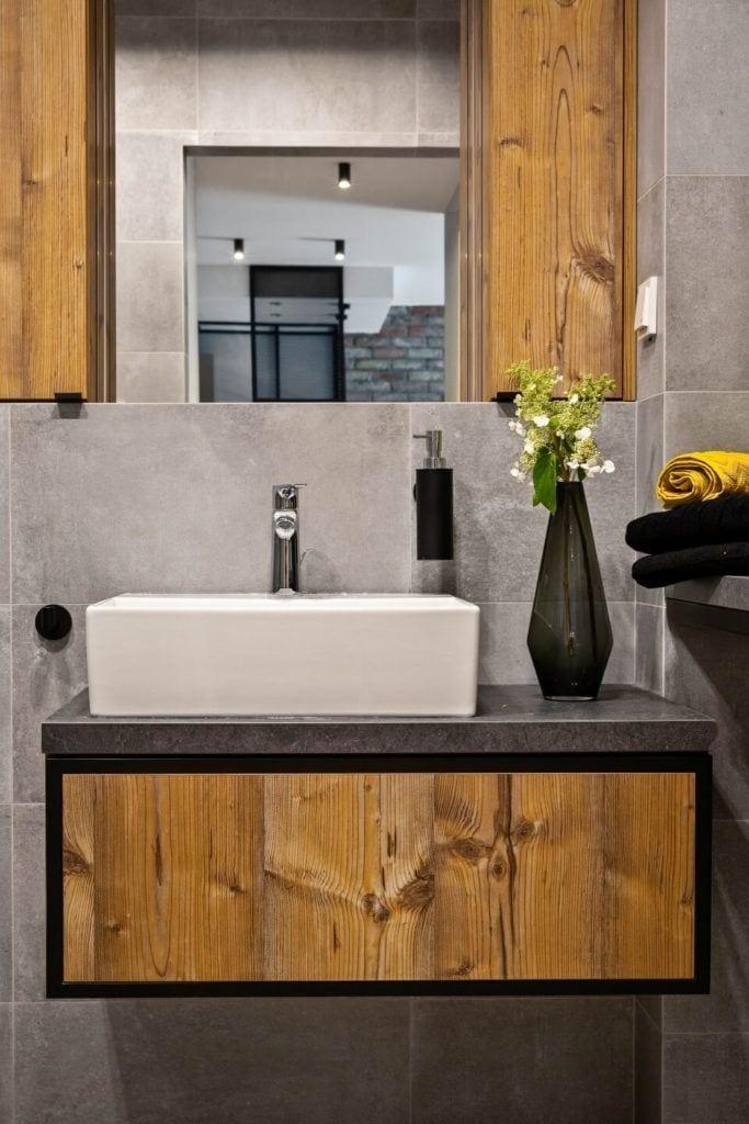Łazienka w stylu soft industrialnym z szafkami z drewnianymi frontami