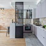 Połączenie jasnej kuchni z salonem ze ścianą z cegły