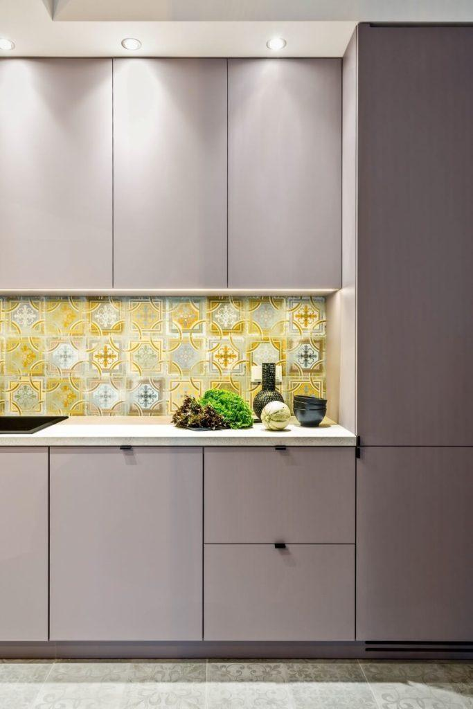 Kuchnia z białą zabudową i płytkami w stylu orientalnym w apartamencie w sercu Warszawy