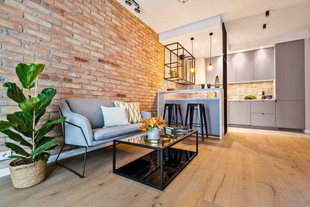 Salon z drewnianą podłogą i ścianą z cegły
