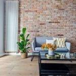 Salon w stylu soft industrialnym ze ścianą z cegły pochodzącą z rozbiórki