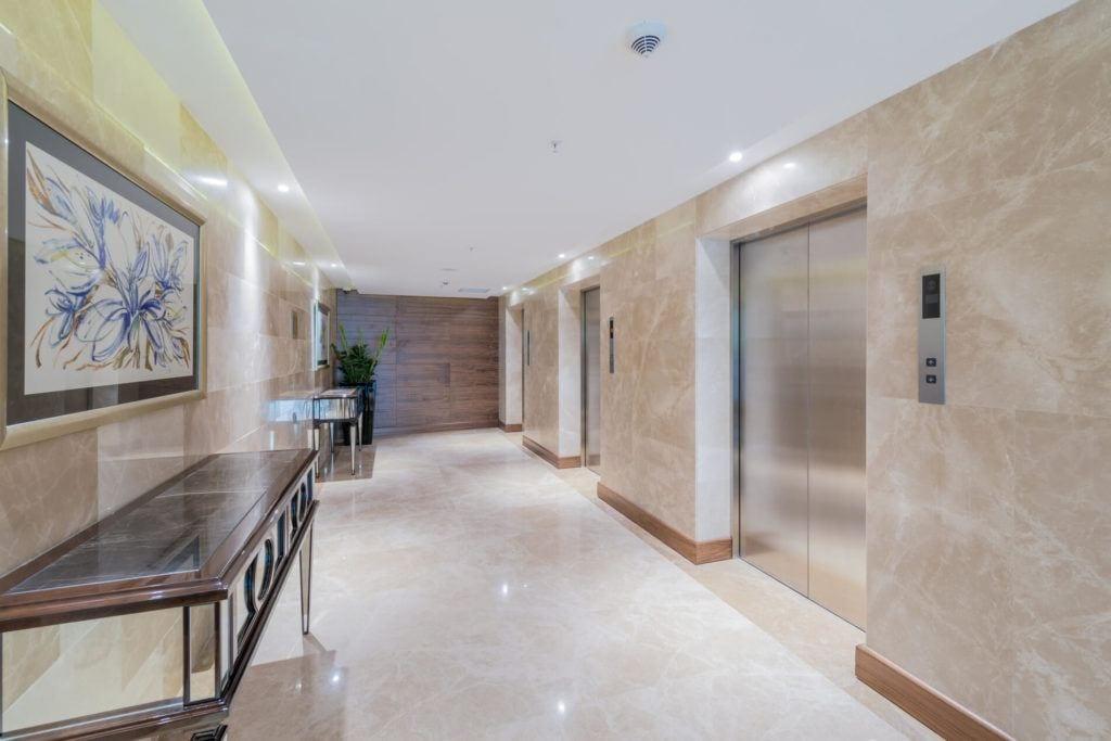 Marmur Crema Marfil w holu przed windami