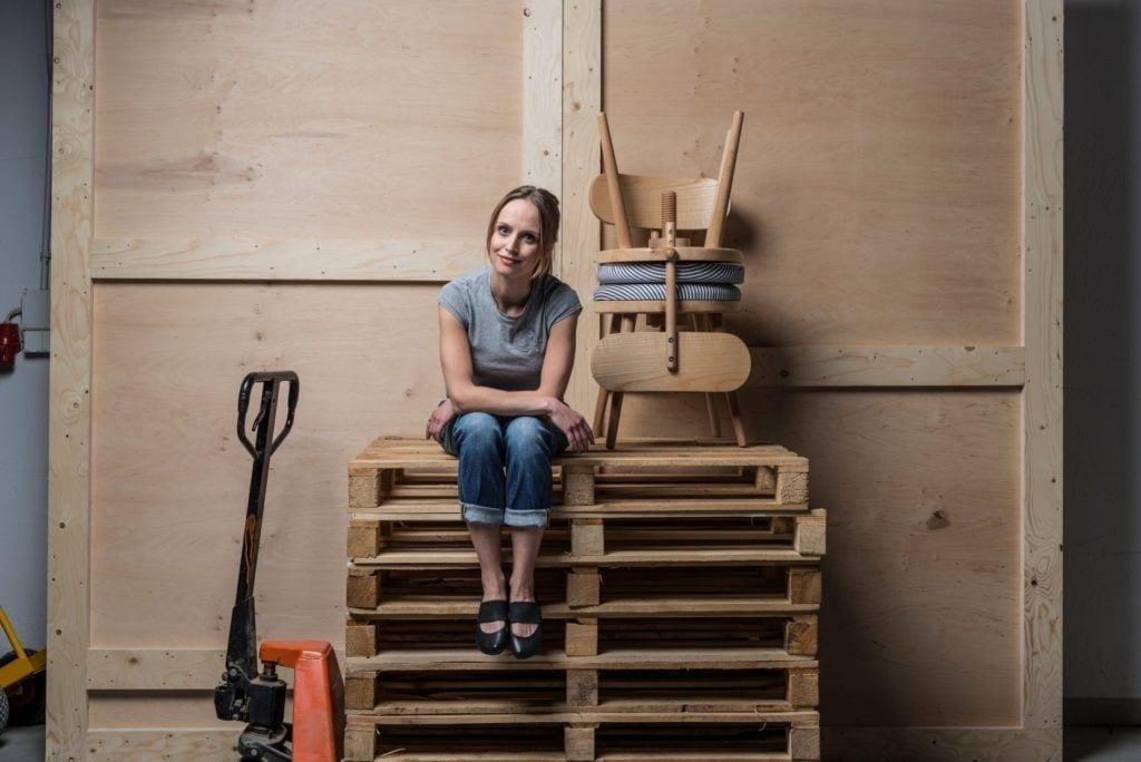 Projektantka Joanna Leciejewska siedząca na paletach