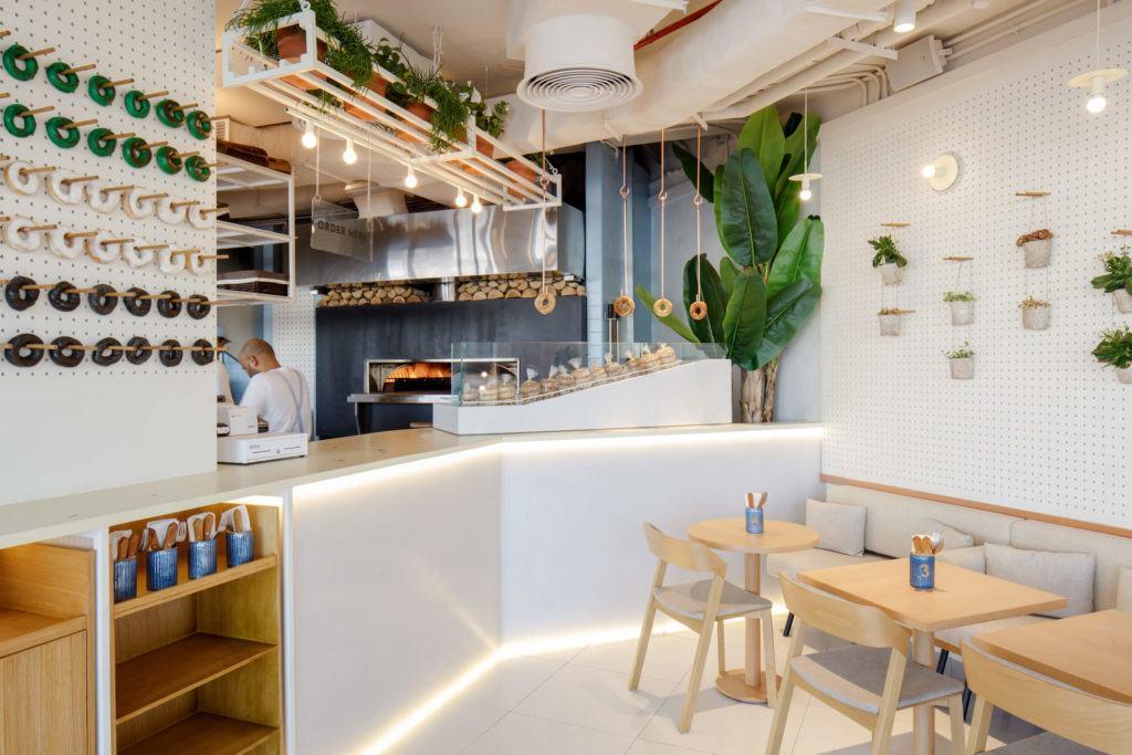 Jasne wnętrze kawiarnii Bagel Yard Cafe w Dubaju projektu H2R Design