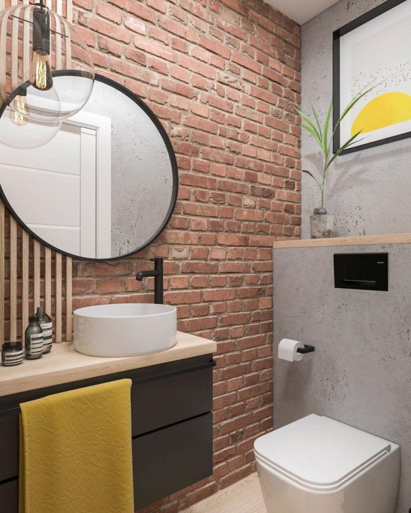 Łazienka z okrągłym lustrem i ścianą z cegły w łódzkim mieszkaniu projektu Marty Ogrodowczyk i Marty Piórkowskiej