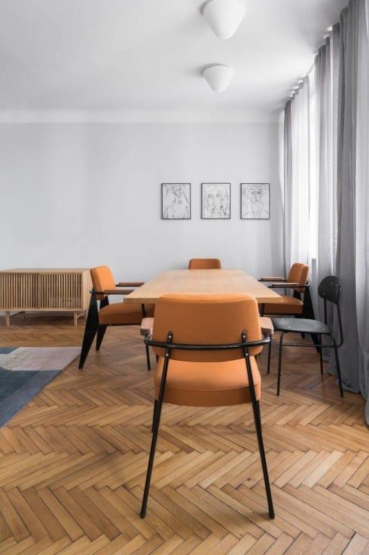 Pomarańczowe fotele przy stole w salonie w mieszkaniu w kamienicy