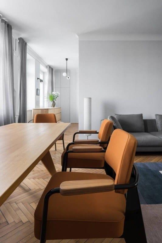 Pomarańczowe fotele w salonie w mieszkaniu projektu Loft Kolasiński